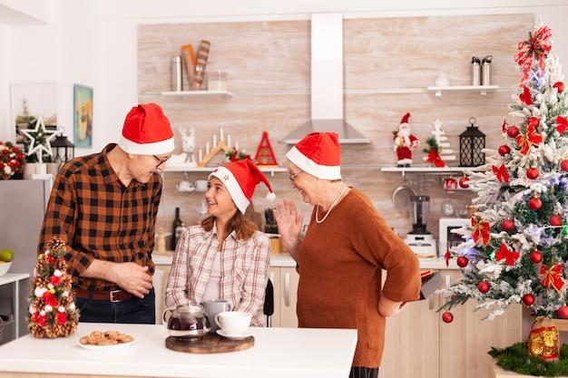 Szczęśliwi dziadkowie zaskakują wnuczce prezentem świątecznym ze wstążką na nim