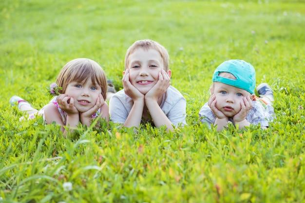 Szczęśliwi dzieci kłamają na zielonej trawie w łące