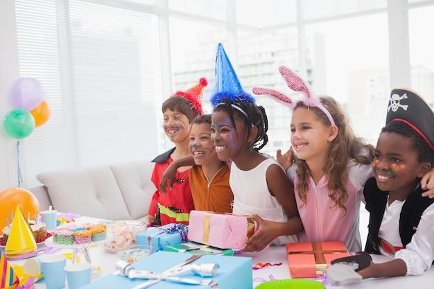 Szczęśliwi dzieci przy galanteryjnej sukni przyjęciem urodzinowym