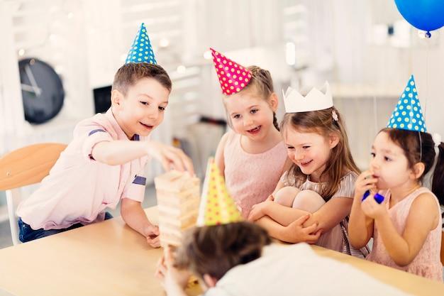 Szczęśliwi dzieciaki bawić się grę przy stołem