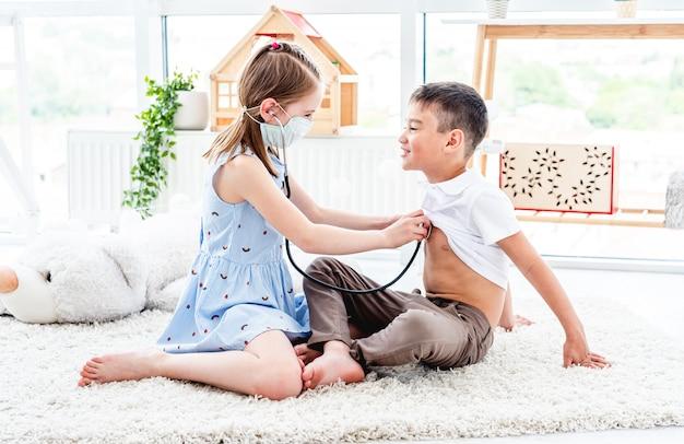 Szczęśliwi dzieciaki bawić się lekarkę w lekkim pokoju