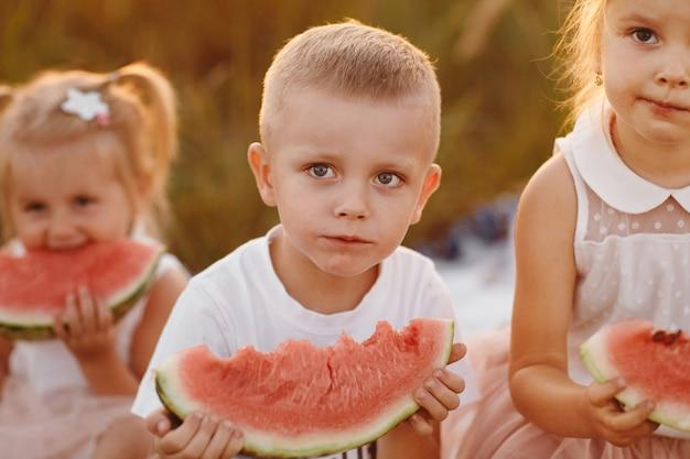 Szczęśliwi dzieciaki je arbuza w lecie przy zmierzchem w polu.