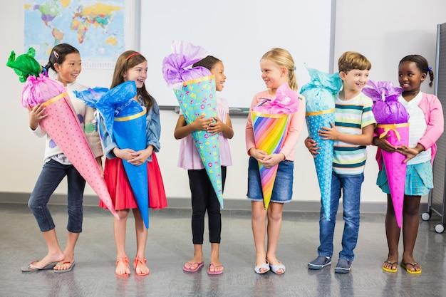 Szczęśliwi dzieciaki trzyma prezenty w sala lekcyjnej