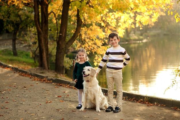 Szczęśliwi dzieciaki z psem w parku w jesieni