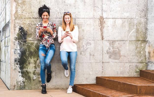Szczęśliwi dziewczyna najlepsi przyjaciele ma zabawę outdoors z mobilnym mądrze telefonem