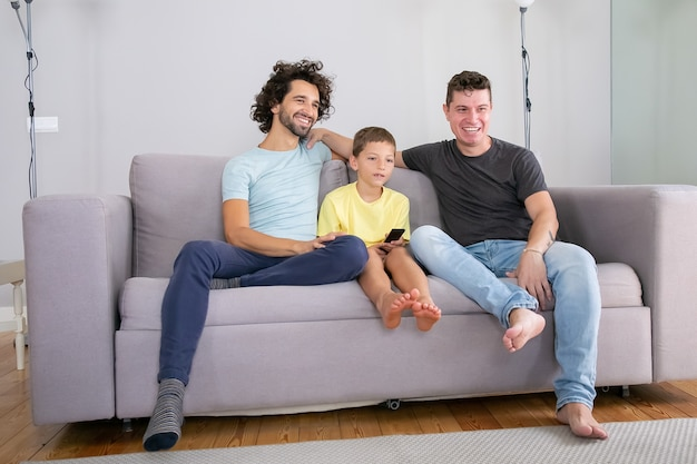 Szczęśliwi homoseksualni rodzice i syn siedzą razem na kanapie w domu i oglądają komedię w telewizji, odwracają wzrok, uśmiechają się i śmieją. pojęcie rodziny i rodzicielstwa