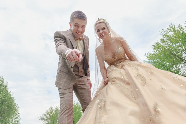 Szczęśliwi i piękni nowożeńcy spacerujący po parku. ślub w plenerze.