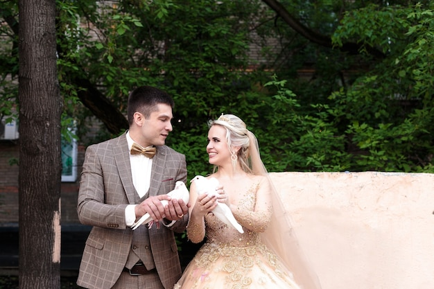 Szczęśliwi i piękni nowożeńcy trzymają gołębie. ślub w plenerze.