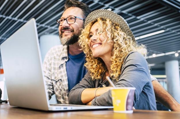 Szczęśliwi i weseli ludzie para nowoczesnych młodych dorosłych pracowników z technologią laptop komputer połączony styl życia i cyfrowe biuro nomadów inteligentna praca wszędzie podróżuje modne życie kobieta i mężczyzna