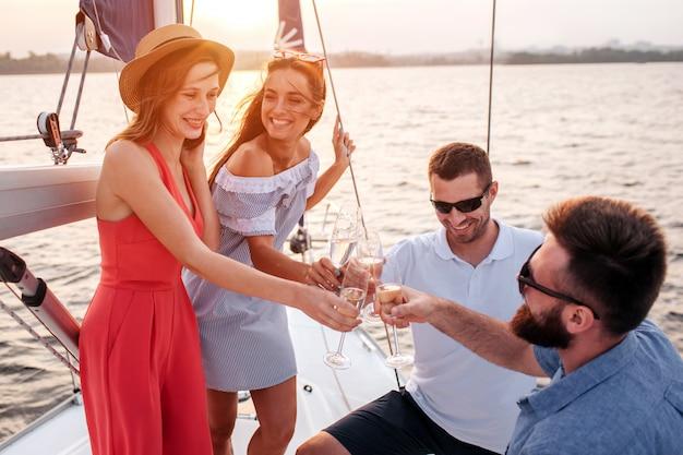 Szczęśliwi i zadowoleni ludzie stoją na pokładzie jachtu. kobiety sięgają z kieliszkiem szampana do mężczyzn. brunetka rozmawia i patrzy na inne młode kobiety. mężczyźni noszą okulary przeciwsłoneczne.