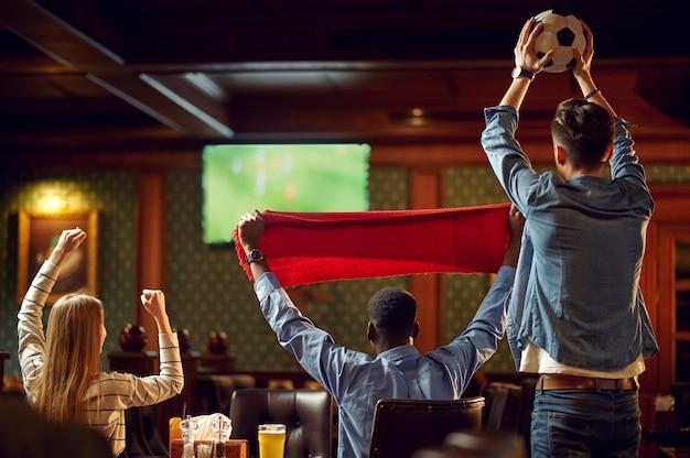 Szczęśliwi kibice z czerwonym szalikiem i piłką oglądający transmisje telewizyjne z meczu, przyjaciele w barze