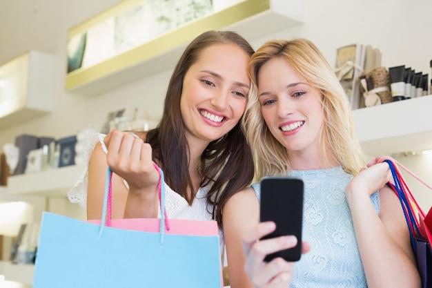 Szczęśliwi kobieta przyjaciele patrzeje smartphone