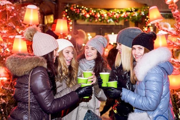 Szczęśliwi kobieta przyjaciele świętuje przy bożymi narodzeniami wprowadzać na rynek