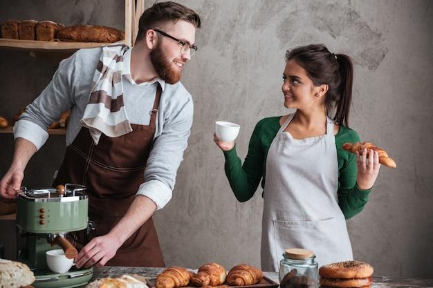 Szczęśliwi kochający para piekarzi pije kawę