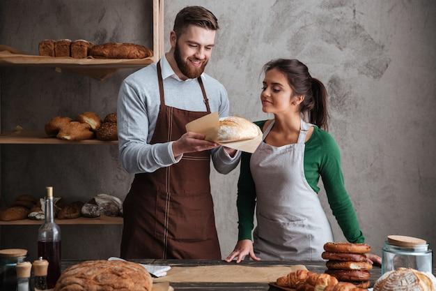 Szczęśliwi kochający para piekarzi stoi przy piekarni mienia chlebem