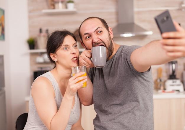 Szczęśliwi kochankowie biorąc selfie z telefonem rano pijąc sok pomarańczowy i kawę. radosny żonaty mąż i żona robiąc śmieszne miny podczas robienia zdjęć podczas śniadania w kuchni.