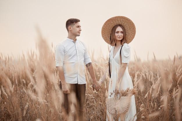 Szczęśliwi kochankowie chodzą razem w terenie. para zakochanych w polu pod koniec lata. brunetka w lekkiej sukience, słomkowy kapelusz i torebka. historia miłosna.