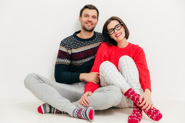 Szczęśliwi kochankowie siedzą razem w białym studio, noszą codzienne ubrania