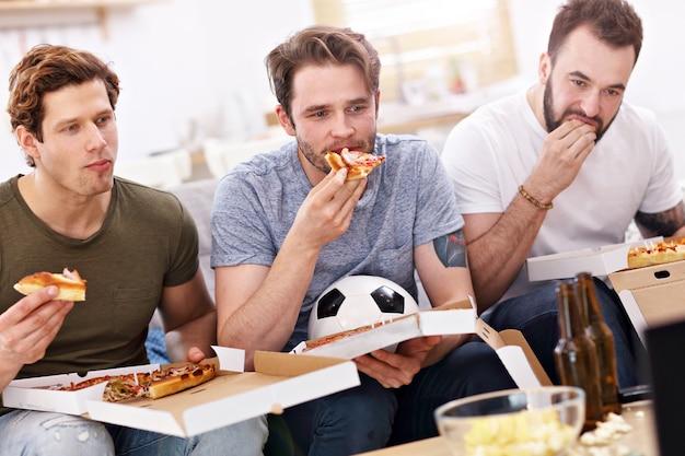 Szczęśliwi koledzy dopingują i oglądają sport w telewizjit