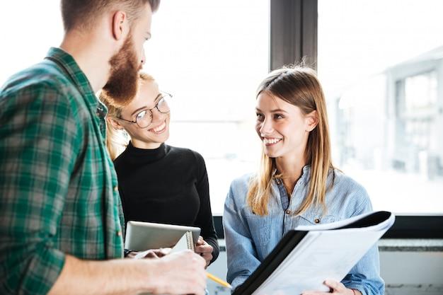 Szczęśliwi koledzy w biurze rozmawia ze sobą trzymając folder