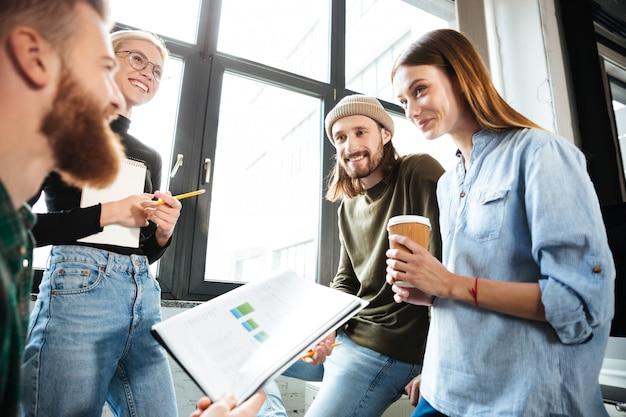 Szczęśliwi koledzy w biurze rozmawiają ze sobą