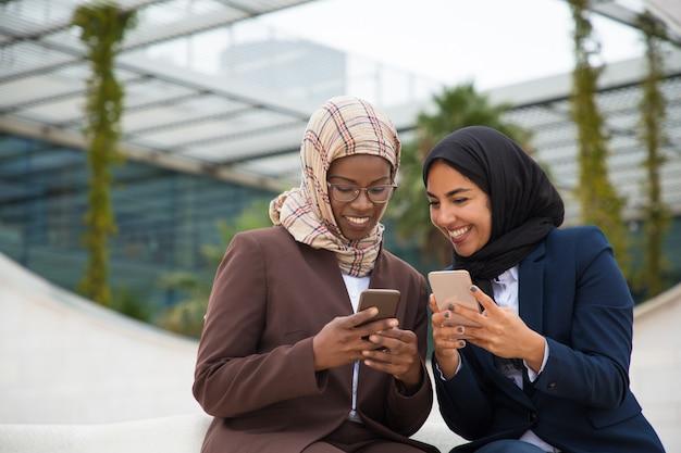 Szczęśliwi koledzy z biura na czacie na smartfonach