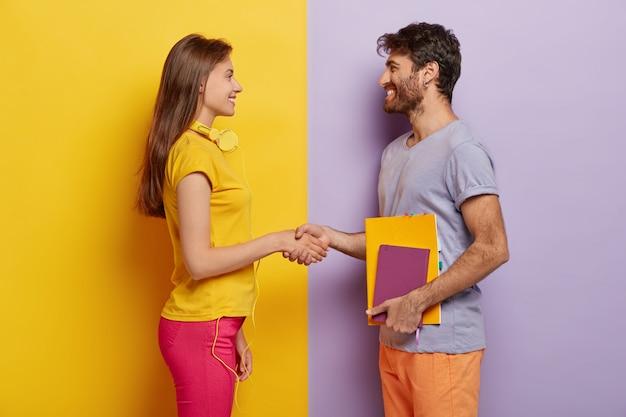 Szczęśliwi koledzy z grupy spotykają się po wakacjach, ściskają sobie ręce, zgadzają się pracować razem jako zespół, stoją z profilu, urocza kobieta ze słuchawkami spotyka przyjaciółkę. nieogolony młody człowiek trzyma notatnik rozmowy z kobietą