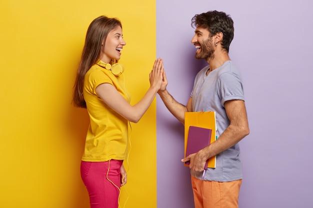 Szczęśliwi koledzy z grupy stoją naprzeciw siebie, ściskają ręce, zadowoleni, że kończą wspólne zadanie, ubrani w zwykłe ubrania, trzymają notatnik do pisania
