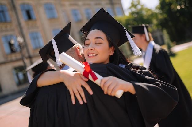 Szczęśliwi koledzy z grupy w czapkach mistrzów przytulający się na balu maturalnym przed uniwersytetem