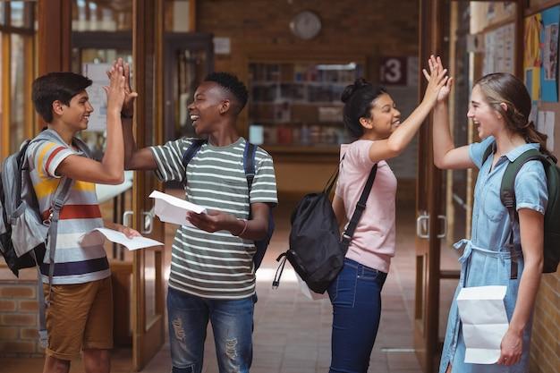Szczęśliwi koledzy z klasy przybijają sobie piątkę na korytarzu