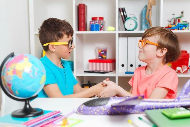 Szczęśliwi koledzy z klasy robią uścisk dłoni. powrót do koncepcji szkoły. chłopcy razem odrabiają lekcje. szczęśliwi studenci w miejscu pracy. dzieci w wieku szkolnym uczące się razem w klasie.
