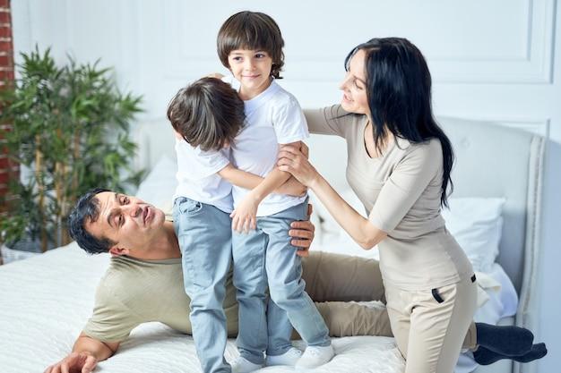 Szczęśliwi latynoscy chłopcy bawią się razem z rodzicami, stojąc na łóżku w domu. szczęśliwe dzieciństwo, koncepcja rodzicielstwa