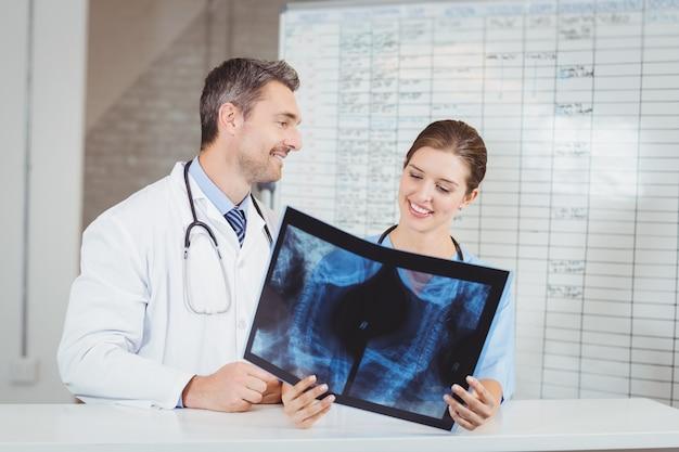 Szczęśliwi lekarze badający promieniowanie rentgenowskie według mapy