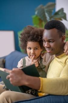 Szczęśliwi ludzie. afroamerykanin czyta interesującą książkę swojej przytulającej się małej uważnej córce siedzącej na kanapie w domu