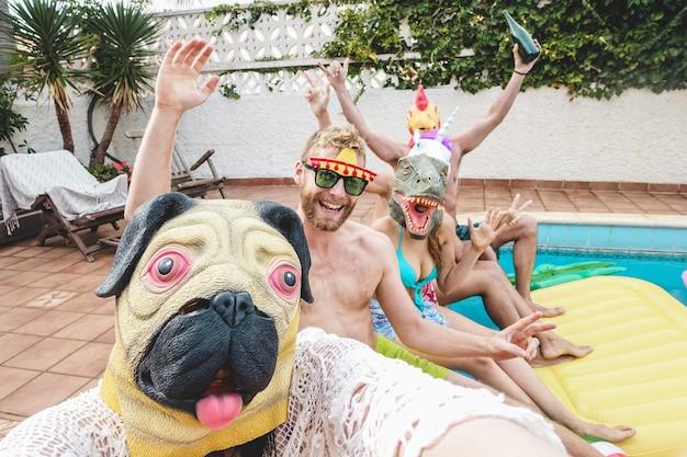 Szczęśliwi ludzie bawią się na imprezie przy basenie, nosząc śmieszne maski zwierząt
