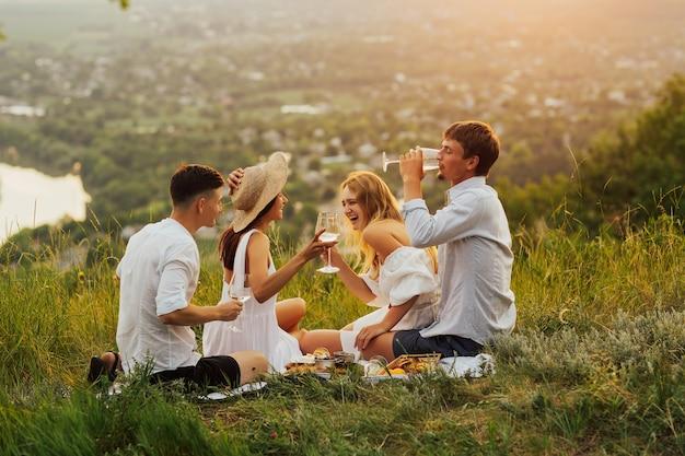 Szczęśliwi ludzie bawią się, uśmiechają się i piją białe wino. młodzi przyjaciele w letni dzień siedzą na szczycie góry.