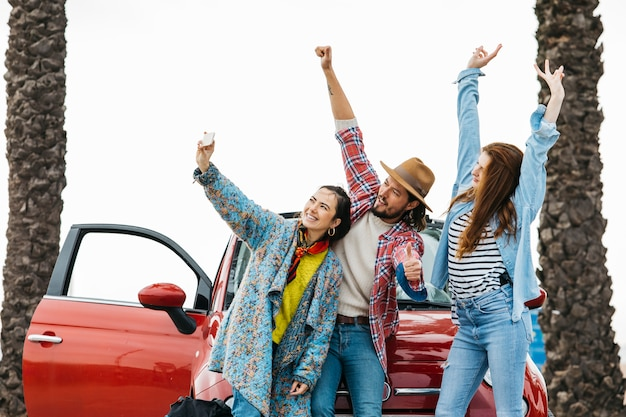 Szczęśliwi ludzie bierze selfie blisko czerwonego samochodu w ulicie