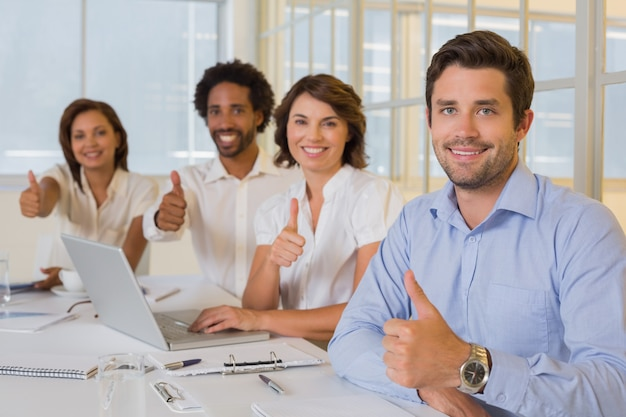 Szczęśliwi ludzie biznesu gestykuluje aprobaty w spotkaniu