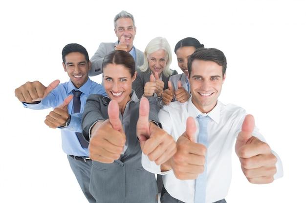 Szczęśliwi ludzie biznesu patrzeje kamerę z aprobatami