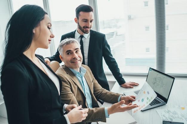 Szczęśliwi ludzie biznesu rozmawiający przy laptopie