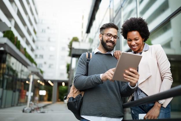 Szczęśliwi ludzie biznesu, studenci bawiący się, uśmiechający się, rozmawiający w mieście