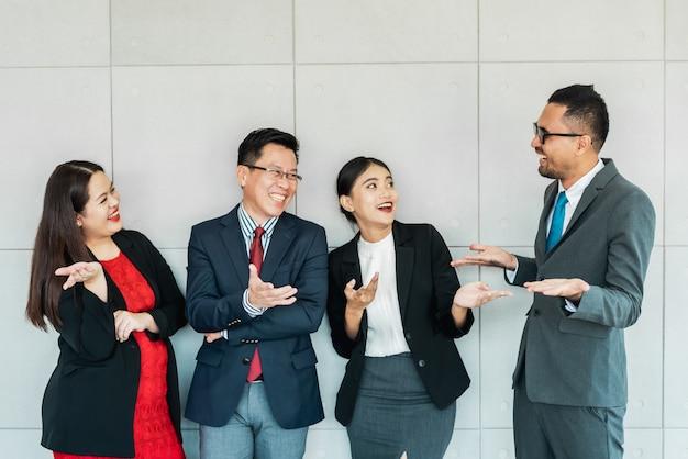 Szczęśliwi ludzie biznesu uśmiechnięci i śmieją się w ich biurze