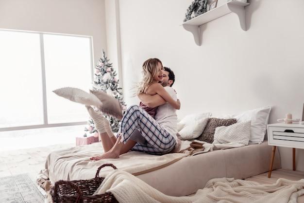 Szczęśliwi ludzie. długowłosa piękna kobieta i jej ciemnowłosy mąż czują się radośnie, gdy się przytulają