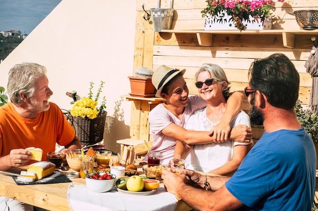 Szczęśliwi ludzie dorośli i jeden nastolatek uśmiechając się i jedząc. wielopokoleniowa rodzina wspólnie spożywa śniadanie. starsza para z synem i siostrzeńcem. drewniany stół i tło