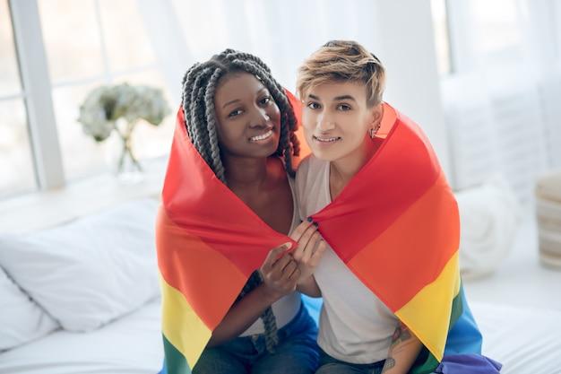 Szczęśliwi ludzie. dwie młode dziewczyny z tęczową flagą uśmiecha się pozytywnie