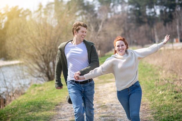 Szczęśliwi ludzie. młoda dorosła entuzjastyczna kobieta biegająca z długimi rudymi włosami i uważnym mężczyzną trzymającym rękę w naturze w słoneczny dzień