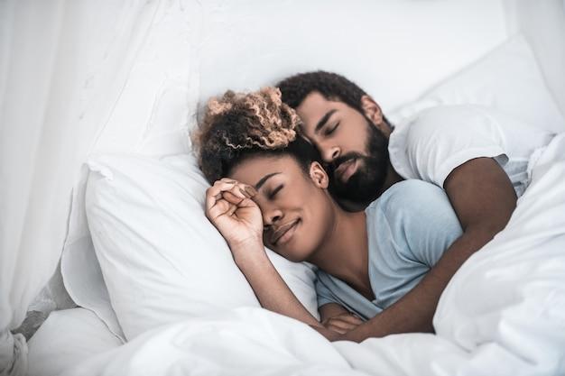 Szczęśliwi ludzie. młody dorosły ciemnoskóry mężczyzna przytulanie śliczną żonę śpiącą pod białym kocem w sypialni