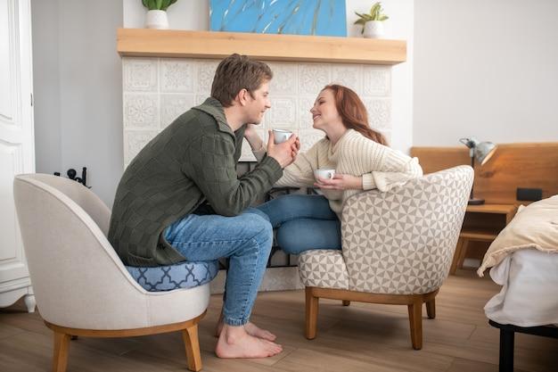 Szczęśliwi ludzie. młody dorosły uśmiechnięty mężczyzna i dotykająca ładna kobieta pijąca kawę naprzeciwko siebie przy kominku w domu
