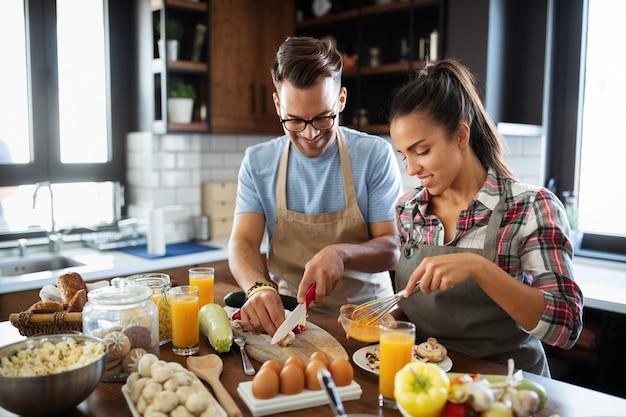 Szczęśliwi ludzie, para przyjaciół gotujących razem jedzenie w swojej kuchni na poddaszu w domu