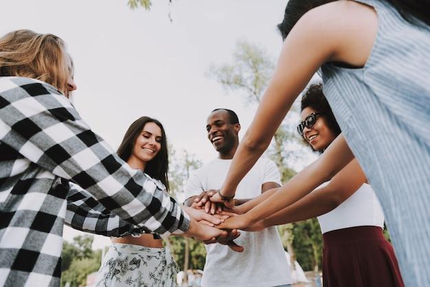 Szczęśliwi ludzie pracy zespołowej przyjaciół układania rąk